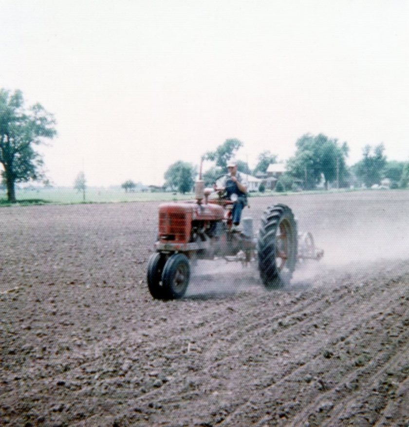 Clyde Planting corn in field just north of Hicks House.